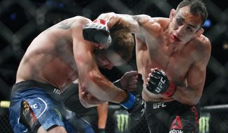Tony Ferguson, right, punches Donald Cerrone, left, during their lightweight mixed martial arts bout at UFC 238, Saturday, June 8, 2019, in Chicago. (AP Photo/Kamil Krzaczynski)