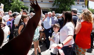 Democratic presidential candidate Bernie Sanders, center, waves to a vendor during the Capital City Pride Fest, on Saturday in Des Moines, Iowa. Mr. Sanders is running  second, behind former Vice President Joseph R. Biden, in his bid for the nomination. (Associated Press)