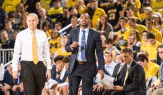 DeAndre Haynes (center) coaches the University of Michigan men's basketball team from the sidelines. Haynes joined the University of Maryland as an assistant coach on Monday, June 10, 2019. (Photo courtesy of Michigan athletics)