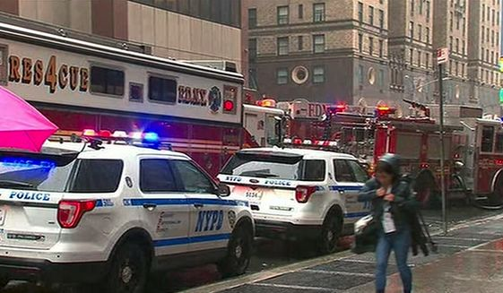 In this photo taken from video, first responders arrive near the scene where a helicopter was reported to have crash landed on top of a building in midtown Manhattan, Monday, June 10, 2019, in New York. (WABC via AP)