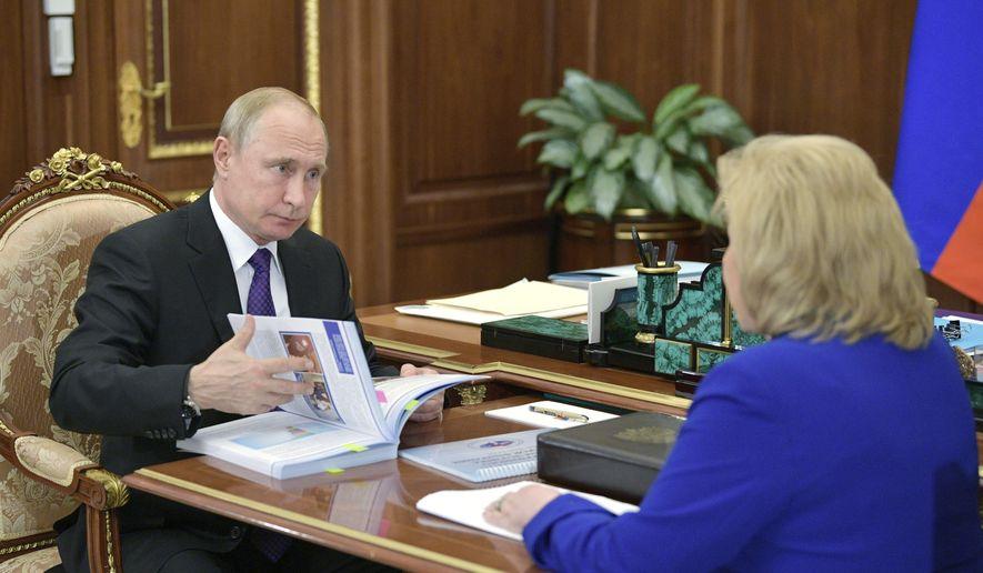 Russian Human Rights ombudsman Tatyana Moskalkova listens to Russian President Vladimir Putin during their meeting in the Kremlin in Moscow, Russia, Monday, June 10, 2019. (Alexei Druzhinin, Sputnik, Kremlin Pool Photo via AP)