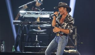 """FILE - In this May 4, 2019 file photo, Tim McGraw performs at the iHeartCountry Festival at the Frank Erwin Center in Austin, Texas. The country musician and a political historian may look like an unlikely duo, but McGraw and Pulitzer Prize-winning author Jon Meacham share a common love of history and music. The two wrote """"Songs of America: Patriotism, Protest and the Music That Made a Nation,"""" out Tuesday, June 11 about the impact music has had on American politics, from wars to cultural movements  (Photo by Jack Plunkett/Invision/AP, File)"""