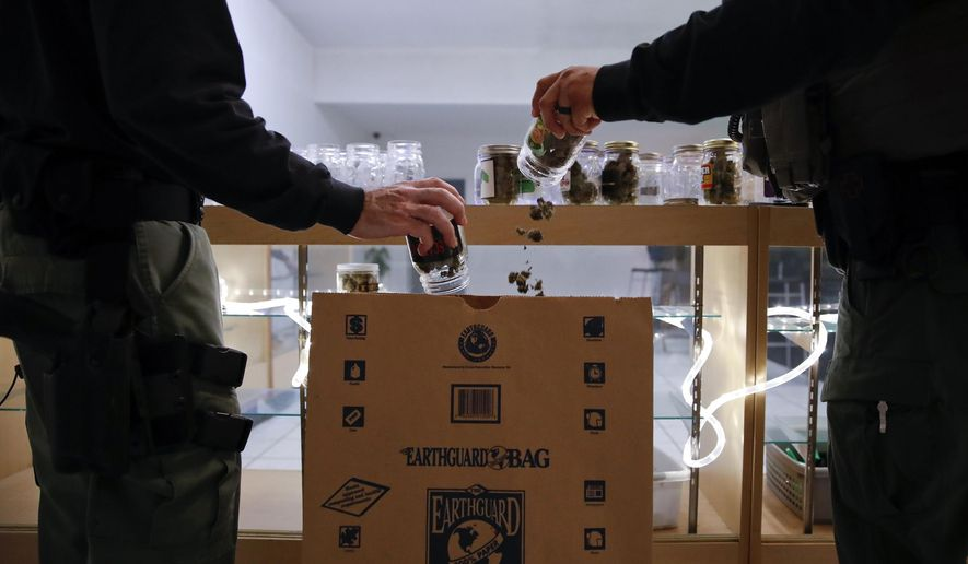 FILE - In this March 15, 2018 file photo, two undercover Los Angeles County sheriff's deputies dump marijuana into an evidence bag during a raid at an illegal marijuana dispensary during a raid in Compton, Calif. The legal marijuana industry is urging Los Angeles City Hall to get tougher with illegal shops that are gouging into their business. Illegal pot shops are widespread throughout Los Angeles, selling cheaper products than their legal rivals because they don't pay taxes. In a letter Monday, June 10, 2019, the industry group Southern California Coalition recommended the city consider seizing cannabis inventory and cash from illegal shops that are found to be selling tainted products. (AP Photo/Jae C. Hong, File)