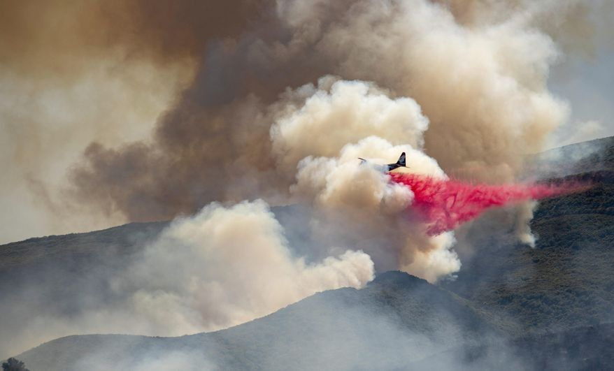 A plane drops fire retardant on a hillside in an attempt to box in flames from a wildfire during the Sand Fire in Rumsey, Calif., Sunday, June 9, 2019. (AP Photo/Josh Edelson)