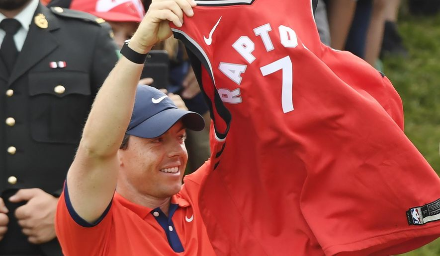 Rory McIlroy, of Northern Ireland, raises a Toronto Raptors jersey on the 18th green after winning the Canadian Open golf championship in Ancaster, Ontario, Sunday, June 9, 2019. (Nathan Denette/The Canadian Press via AP)