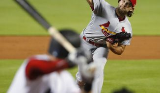 St. Louis Cardinals' Michael Wacha, top, pitches to Miami Marlins' Garrett Cooper during the first inning of a baseball game, Monday, June 10, 2019, in Miami. (AP Photo/Wilfredo Lee)