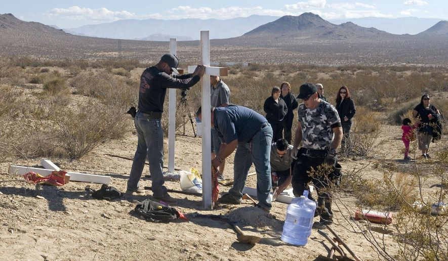 "FILE - In this Nov. 20, 2013, file photo, residents of Victorville, Calif., and surrounding communities place crosses near the graves where the McStay family was found in Victorville, Calif. A jury verdict will be read in the case of a Southern California man charged with killing a family of four and burying their bodies in the desert. The verdict will be read Monday, June 10, 2019, in court in San Bernardino in the quadruple murder case against 62-year-old Charles ""Chase"" Merritt. (James Quigg/The Daily Press via AP, File)"