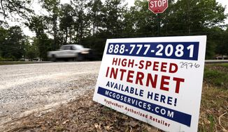 In this May 8, 2019, photo, a car drives past a sign advertising high-speed internet service near Starkville, Miss. In classrooms, access to laptops and the internet is nearly universal. But many students struggle to keep up from home because of the cost of internet service and gaps in its availability. (AP Photo/Rogelio V. Solis)
