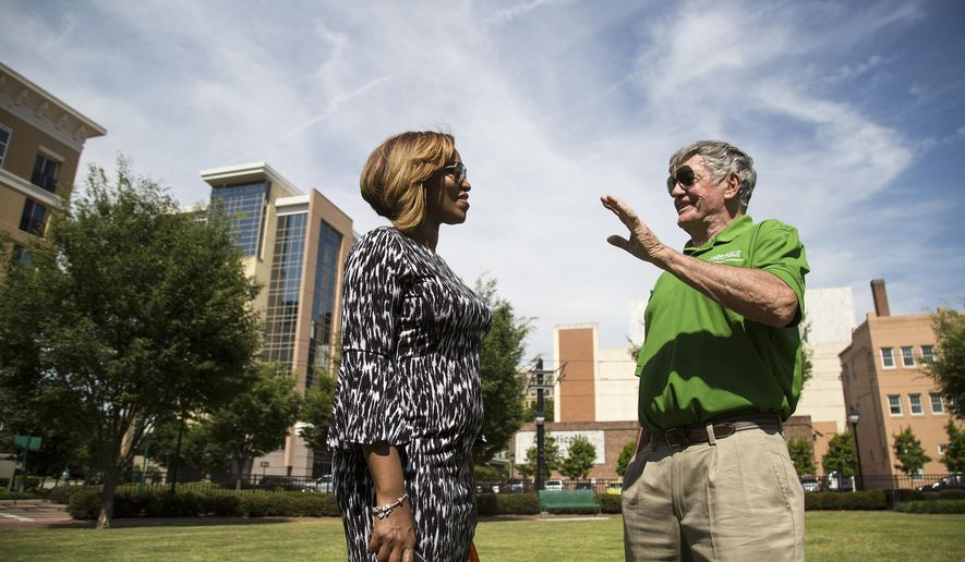 In this May 22, 2019 photo, Jasmine Duncan and Mike O'Hearn talk following a dedication ceremony for Farragut Park in downtown Norfolk, VA. The park's name stands out in Norfolk history, and is perhaps indicative of a shifting attitude: Many public spaces and buildings in the city bear the names of Confederate military men. Farragut's park is the first to recognize a Union officer. (Kaitlin McKeown/The Virginian-Pilot via AP)