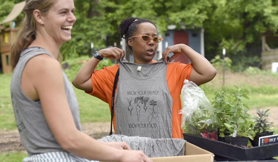 Emma Jagoz, left, founder and co-owner of Moon Valley Farm, smiles as Pam Suarez, of Windsor Mill, holds up a tank top during a plant sale, which the farm holds on Saturdays during the spring. (Steve Ruark/The Baltimore Sun via AP)