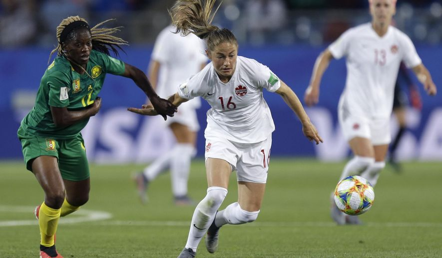 Canada's Janine Beckie, right, and Cameroon's Claudine Meffometou battle for the ball during the Women's World Cup Group E soccer match between Canada and Cameroon in Montpellier, France, Monday, June 10, 2019. (AP Photo/Claude Paris)