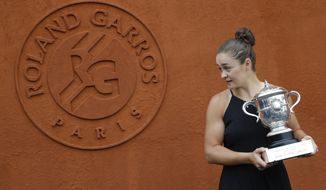 Australia's Ashleigh Barty poses with the trophy during a photo call at the Roland Garros stadium in Paris, Sunday, June 9, 2019. Barty won the French Open tennis tournament women's final on Saturday June 8, 2019. (AP Photo/Michel Euler)