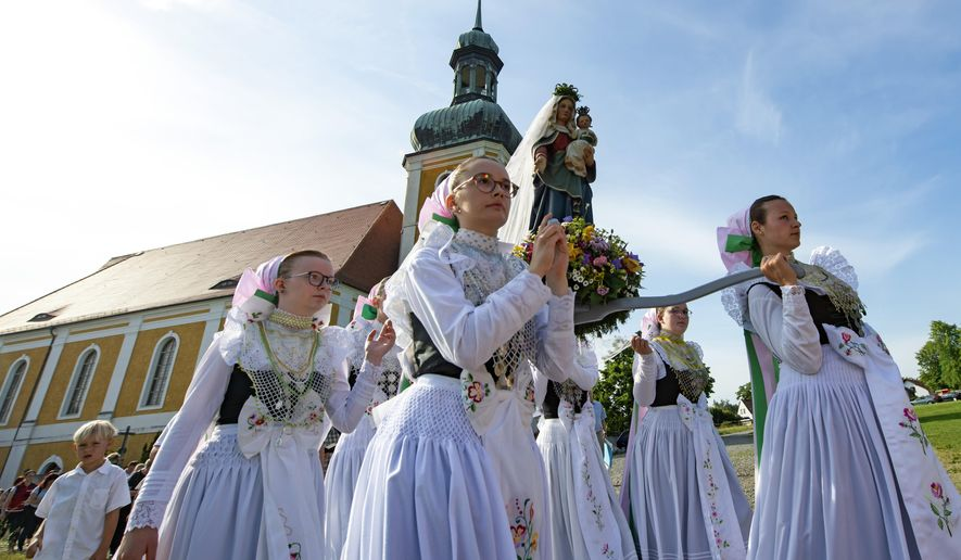 Women dressed in the traditional clothes of the Sorbs carry the statue of Virgin Mary during a procession in front of the Roman Catholic pilgrimage church in Rosenthal, eastern Germany, Monday, June 10, 2019. Traditionally on White Monday catholic faithful Sorbs, a Slavic minority near the German-Polish border, celebrate an open-air mass in the small village east of Dresden. (AP Photo/Jens Meyer) **FILE**