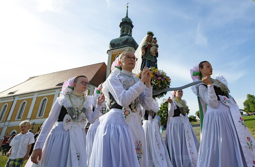 Women dressed in the traditional clothes of the Sorbs carry the statue of Virgin Mary during a procession in front of the Roman Catholic pilgrimage church in Rosenthal, eastern Germany, Monday, June 10, 2019. Traditionally on White Monday catholic faithful Sorbs, a Slavic minority near the German-Polish border, celebrate an open air mass in the small village east of Dresden. (AP Photo/Jens Meyer)