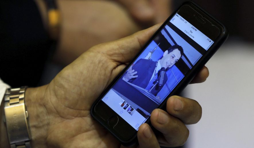 """In this July 18, 2017, file photo, Ziad Zakka, brother of Nizar Zakka who is imprisoned in Iran, shows a photo of his brother on his cellular telephone in Beirut, Lebanon. Iranian state television reported Monday, June 10, 2019, that Zakka, a Lebanese national and a U.S. permanent resident held for years in Tehran, """"will be released in the coming hours."""" (AP Photo/Bilal Hussein, File)"""