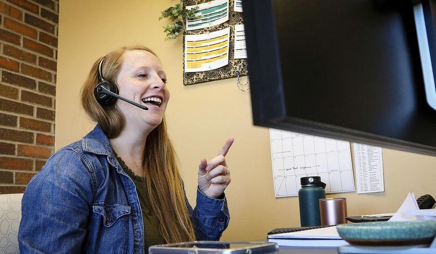 In a Thursday, June 6, 2019 photo, Audrey Nordine, Black Hills Program Coordinator for the Helpline Center, works in her office in Rapid City.  (Adam Fondren/Rapid City Journal via AP)
