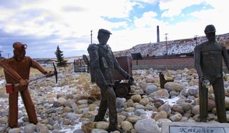 FILE - This Dec. 13, 2016, file photo, shows the former Anaconda smelter smokestack behind sculptures of miners at the Anaconda Smelter Stack State Park viewing area in Anaconda, Montana. Residents in the nearby community of Opportunity are suing to get the Atlantic Richfield Co. to do a more thorough cleanup of arsenic in residential yards. The Montana Supreme Court ruled in December 2017 that they could move forward with their 2008 lawsuit. Arco appealed, arguing a state lawsuit shouldn't be able to interfere with an ongoing cleanup. The U.S. Supreme Court said Monday, June 10, 2019, it will hear the appeal. (AP Photo/Matt Volz, File)