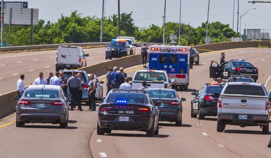 Crews work the scene a fatal officer involved shooting on I-35 in Oklahoma City Okla. on Monday, June 10, 2019. (Chris Landsberger/The Oklahoman via AP)