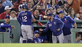 Texas Rangers' Rougned Odor (12) is congratulated after scoring on a single by Danny Santana during the sixth inning of a baseball game against the Boston Red Sox at Fenway Park in Boston, Monday, June 10, 2019. (AP Photo/Charles Krupa)