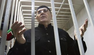 FILE - In this Monday, March 18, 2019 file photo, Oyub Titiev, the head of a Chechnya branch of the prominent human rights group Memorial, gestures while standing behind bars in court after a hearing in Shali, Russia. A court in Russia's province of Chechnya has on Monday, June 10, 2019 ruled to grant early release to Titiyev, a prominent rights activist whose conviction has drawn an international outcry. (AP Photo/Musa Sadulayev, File)