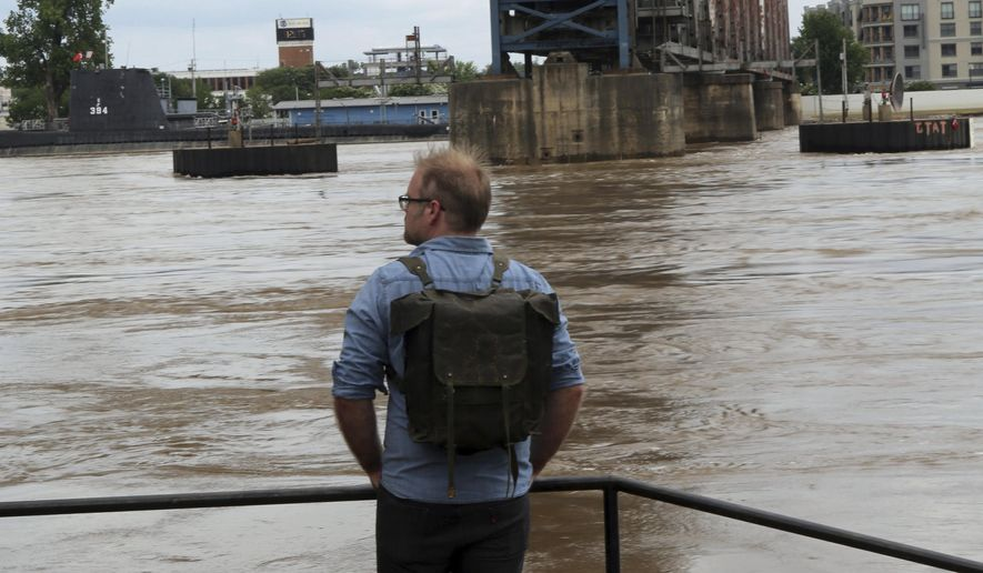 In this Sunday, June, 9, 2019 photo, Josh Vanwie from Denver, Colo., watches the Arkansas River from Riverfront Park in Little Rock, Ark. Authorities say that even though the Arkansas River is now receding and conditions are improving, the water is still dangerous and should be avoided. (Jeff Mitchell, Arkansas Democrat-Gazette via AP)