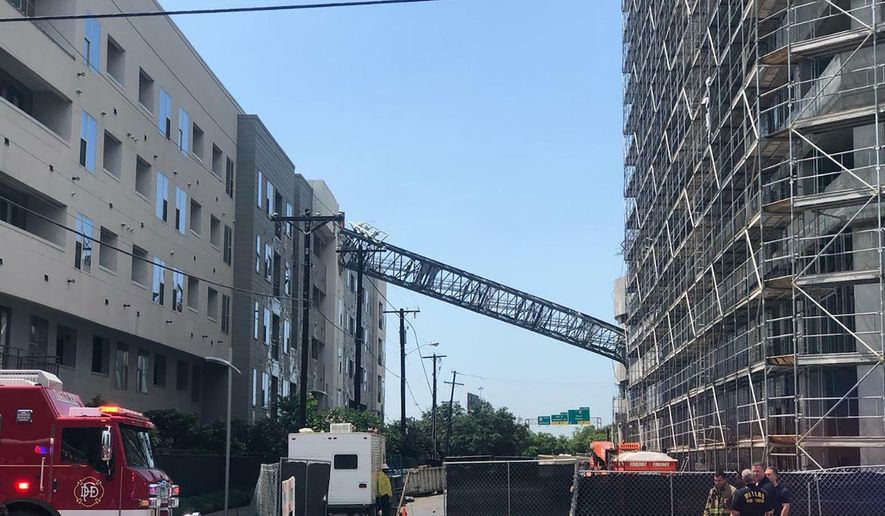 This photo taken and provided by Michael Santana shows a construction crane toppling on an apartment building as it was buffeted by high winds during a storm in Dallas, Texas, Sunday, June 9, 2019. (Michael Santana via AP)