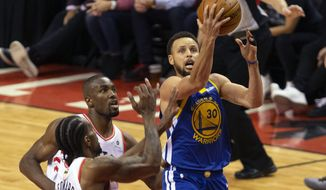 Golden State Warriors guard Stephen Curry (30) drives pass Toronto Raptors center Serge Ibaka (9) and Toronto Raptors forward Kawhi Leonard (2) in the fourth quarter of Game 5 of the NBA Finals in Toronto on Monday June 10, 2019. (Chris Young/The Canadian Press via AP) ** FILE **