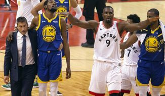 Golden State Warriors forward Kevin Durant (35) walks off the court after sustaining an injury as Toronto Raptors center Serge Ibaka (9) gestures to the crowd during first half basketball action in Game 5 of the NBA Finals in Toronto on Monday, June 10, 2019. (Chris Young/The Canadian Press via AP)