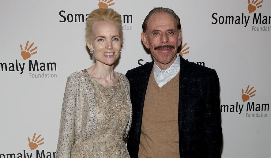 In this Oct. 23, 2013, file photo, artist Peter Max, right, and his wife Mary Max, left, attend the Somaly Mam Foundation Gala in New York. Authorities say Mary Max, 53, was found dead Sunday, June 9, 2019, in New York, of a suspected suicide amid a family fight over her husbands work. Her death comes two weeks after The New York Times published a story detailing legal battles over the work of Peter Max, a prolific creator of colorful, psychedelic art who is now living with dementia at age 81.  (Photo by Andy Kropa/Invision/AP, File)