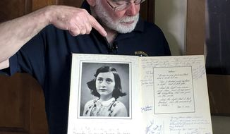 In this June 7, 2019 photo, Ryan Cooper holds a 1972 portion of a diary that he wrote when he visited Otto Frank, the father of the famed Holocaust victim and diarist Anne Frank, at his home in Yarmouth, Mass. The diary includes a photo of Anne Frank and the autographs of other people he met who knew her. Cooper has donated a trove of letters and mementos he received from Otto Frank to the U.S. Holocaust Memorial Museum ahead of the 90th anniversary of Anne Frank's birthday. (AP Photo/Philip Marcelo)