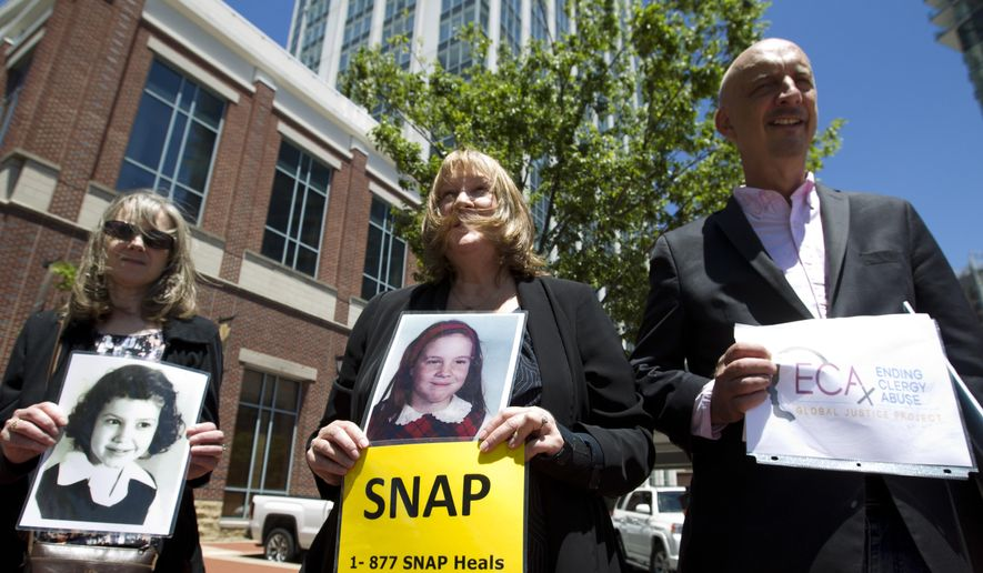 Becky Ianni, center, a victim of priest abuse, holds a picture of her younger self along with other demonstrators outside the venue where the United States Conference of Catholic Bishops 2019 Spring meetings are being held in Baltimore, Tuesday, June 11, 2019.  Ianni says she was 8-years-old when the priest of her family parish began to abuse her. (AP Photo/Jose Luis Magana)