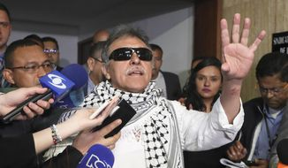 Former FARC rebel Jesus Santrich talks to journalists after swearing in to take his congressional seat in Bogota, Colombia, Tuesday, June 11, 2019. Santrich was unable to take up his seat in congress last year when he was jailed awaiting extradition to the U.S. on drug charges, but was released in a decision by the special peace tribunal. (AP Photo/Fernando Vergara)