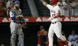 Los Angeles Angels' Mike Trout, right, points after hitting a two-run home run with Los Angeles Dodgers catcher Russell Martin watching during the seventh inning of a baseball game against the Los Angeles Dodgers in Anaheim, Calif., Monday, June 10, 2019. (AP Photo/Alex Gallardo)