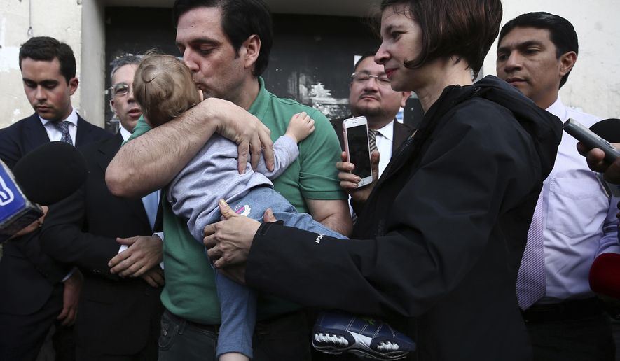 U.S. citizen Paul Ceglia kisses his son Orion held by his wife Marie as he is released from jail in Quito, Ecuador, Tuesday, June 11, 2019. Ecuador released the New York man and turned down an extradition request from the United States, where he was arrested after falsely claiming he was owed half-ownership of Facebook. (AP Photo/Soledad Nunez)