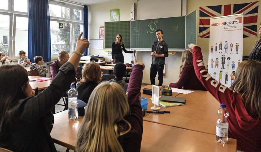 Senior students and media scouts Leon Zielinski and Chantal Hueben, in the background, teach younger pupils during a lesson in social media and internet at a comprehensive school in Essen, Germany, Monday, March 18, 2019.  According to experts and teachers the peer projects in which teenagers teach their younger schoolmates how to stay safe and sane online have proven to be especially successful in Germany. (AP Photo/Martin Meissner)
