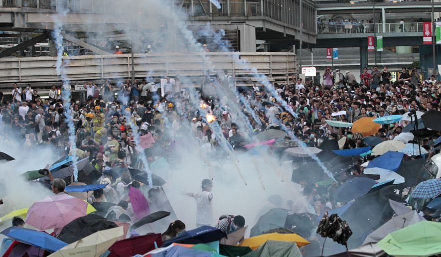 In this Sunday, Sept. 28, 2014, file photo, riot police launch tear gas into the crowd as thousands of protesters surround the government headquarters in Hong Kong. Hong Kong police used tear gas on Sunday and warned of further measures as they tried to clear thousands of pro-democracy protesters gathered outside government headquarters in a challenge to Beijing over its decision to restrict democratic reforms for the city. (AP Photo/Wally Santana, File)