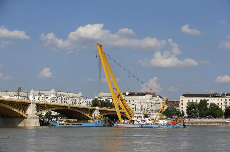A crane float on the Danube river under the Margaret Bridge where a sightseeing boat capsized in Budapest, Hungary, Monday, June 10, 2019. A huge floating crane is in place at Margit Bridge as preparations continue to lift the boat off the river floor. (AP Photo/Darko Bandic)