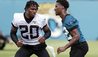 Jacksonville Jaguars cornerback Jalen Ramsey (20) performs a drill with wide receiver Dede Westbrook, right, during an NFL football practice, Tuesday, June 11, 2019, in Jacksonville, Fla. (AP Photo/John Raoux)