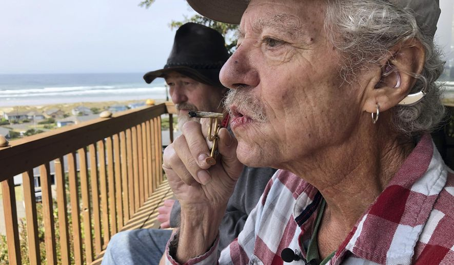 ADVANCE FOR PUBLICATION ON TUESDAY, JUNE 11, AND THEREAFTER - In this April 25, 2019, photo, two-time cancer survivor and medical marijuana cardholder Bill Blazina, 73, smokes a marijuana joint on the deck of his neighbor's home in Waldport, Ore. Blazina also uses a high-potency marijuana oil as a medical marijuana patient but he can't afford it at a recreational marijuana store. Blazina has learned how to make his own oil in a rice cooker after watching online videos. (AP Photo/Gillian Flaccus)