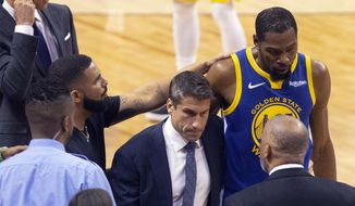 Golden State Warriors forward Kevin Durant, right, is consoled by Drake as he walks off the court after sustaining an injury during first half basketball action in Game 5 of the NBA Finals against Toronto Raptors in Toronto, Monday, June 10, 2019. (Chris Young/The Canadian Press via AP) **FILE**