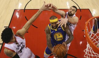 Golden State Warriors center DeMarcus Cousins (0) drives to the net between Toronto Raptors guard Danny Green (14), left, and center Marc Gasol (33) during the first half of Game 5 of the NBA Finals basketball game in Toronto on Monday, June 10, 2019. (Gregory Shamus/Pool Photo via AP, Pool)