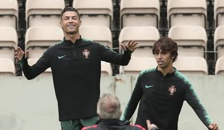 Portugal's Cristiano Ronaldo, left, gestures with Joao Felix, right during a training session at the Bessa stadium in Porto, Portugal, Tuesday, June 4, 2019. Portugal will face Switzerland Wednesday in a UEFA Nations League semifinal soccer match. (AP Photo/Luis Vieira)