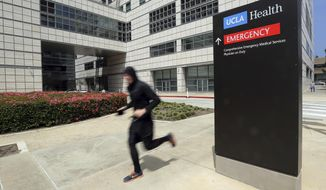 FILE - In this April 26, 2019, file photo, a runner passes the Ronald Reagan UCLA Medical Center on the campus of the University of California, Los Angeles. A woman says she was sexually assaulted by a gynecologist who worked for the University of California, Los Angeles and is upset the school apparently knew about it from her social media post but never contacted her as it investigated other incidents that led to criminal charges. (AP Photo/Reed Saxon, File)