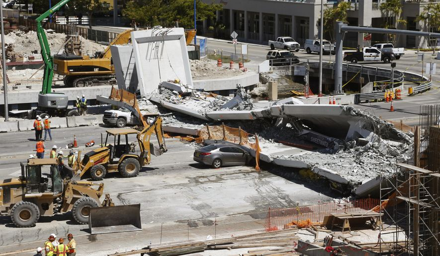FILE - In this March 16, 2018 file photo crushed cars are shown under a section of a collapsed pedestrian bridge near Florida International University in the Miami area. A federal workplace safety agency says engineers had knowledge of extensive cracking and failed to order to close a street and shore up a pedestrian bridge before it collapsed and killed six people at a Miami university last year. On Tuesday, June 11, 2019 a report by the U.S. Occupational Safety and Health Administration concluded the size of the cracks warranted the street be shut down immediately. (AP Photo/Wilfredo Lee)