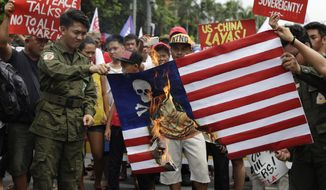Protesters burn a mock U.S. flag during a rally near the U.S. Embassy in Manila, Philippines, to mark the Independence Day on Wednesday, June 12, 2019. The group said they condemn the administration of Philippine President Rodrigo Duterte for it's alleged subservience to the dictates of U.S. and China. They also demanded an end to the Visiting Forces Agreement, VFA, and the Enhanced Defense Cooperation Agreement, EDCA. (AP Photo/Aaron Favila)