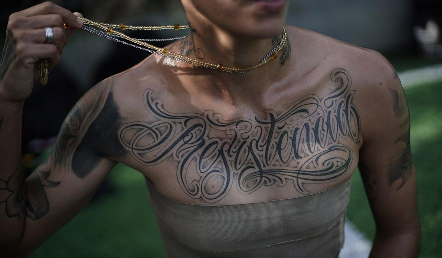 """In this May 13, 2019 photo, transgender Caua Fraga, 23, shows the tattoo on his chest that reads in Portuguese """"Resistance"""", before a training session with the Bigtboys transgender men's football team in Rio de Janeiro, Brazil. For the two dozen Bigtboys players, the training pitch is also one of the few places where they feel at ease and can talk about their experiences, good and bad, without fear. (AP Photo/Silvia Izquierdo)"""