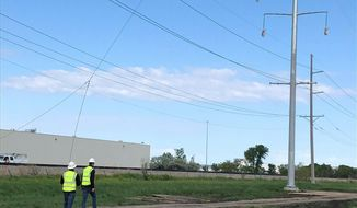 A drone being used by Minnesota-based Xcel Energy for the first time to build transmission lines approaches the first of six power poles , on Wednesday, June 12, 2019, on the north side of Fargo, N.D. The drone was flown by North Dakota-based drone operator SkySkopes, which has built several transmission lines across the country. It took about 20 minutes to string all the wires. (AP Photo/Dave Kolpack)