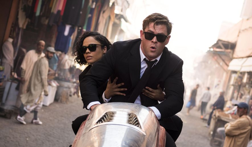 """This image released by Sony Pictures shows Chris Hemsworth, foreground, and Tessa Thompson in a scene from Columbia Pictures' """"Men in Black: International."""" (Giles Keyte/Sony/Columbia Pictures via AP)"""