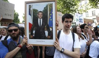 FILE - In this photo taken on Friday May 24, 2019, youths hold the official portrait of French President Emmanuel Macron during a climate march in Paris.Six French activists were convicted Wednesday June 12, 2019 for theft after taking down an official portrait of President Emmanuel Macron to protest his climate change policies they consider as not strong enough. (AP Photo/Michel Euler, File)