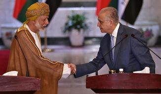 Iraqi Foreign Minister Mohamed Alhakim, right, shakes hands with his visiting Omani counterpart Yusuf bin Alawi, after a press conference at the Ministry of Foreign Affairs Building in Baghdad, Iraq, Wednesday, June 12, 2019. (AP Photo/Hadi Mizban)